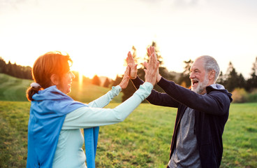 An active senior couple resting after doing exercise in nature at sunset.