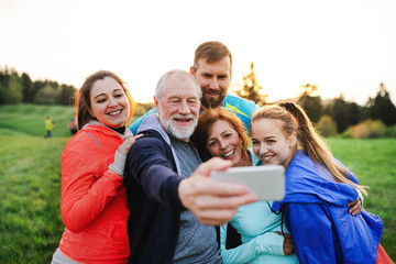 A group of fit and active people resting after doing exercise in nature, taking selfie.