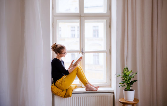 A young female student with a book sitting on window sill, studying.