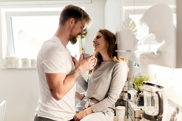 cute girl sitting on a kitchen counter and talking anf flirting with her boyfriend as they´re drinking coffee in the morning