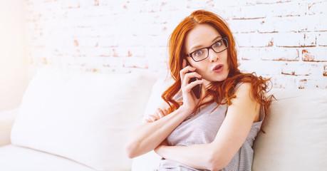 junge überraschte rothaarige, schöne frau beim telefonieren zu hause