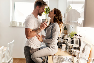 cute caucasian couple spending their morning in the kitchen and drinking coffee