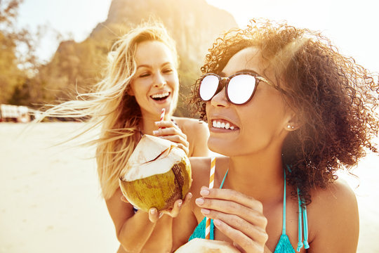 Laughing women walking together along a beach drinking from coco