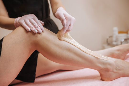 Close-up hands of cosmetologist in gloves applying paste for sugaring depilation on leg, hair removal beauty procedure.