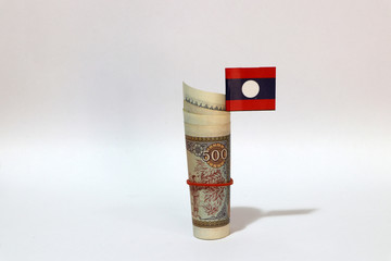 Wall Murals Chicken Rolled banknote money five hundreds Lao Kip and stick with mini Laos flag on white background.