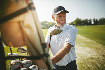 Senior man preparing to play golf on a sunny day