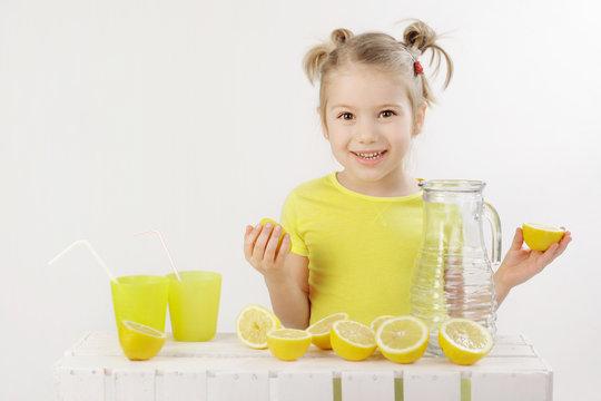 """When life gives you lemons make a lemonade"" 5-year-old girl making lemonade isolated on the white background"
