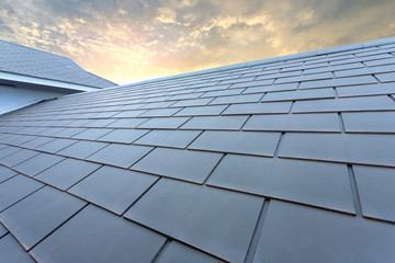 Slate roof against blue sky, Gray tile roof of construction house with blue sky and cloud of the sunset background