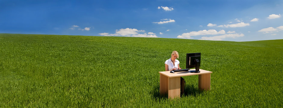 Panorama Businesswoman Using Computer at a Desk In Green Field Banner