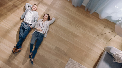 Young Couple are Lying on a Wooden Flooring in an Apartment. They are Happy, Smile and Laugh. Cozy Living Room with Modern Interior, Grey Sofa and Wooden Parquet. Top View Camera Shot. Wall mural