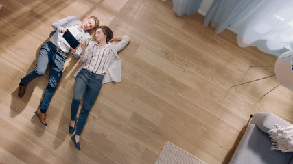 Obraz Young Couple are Lying on a Wooden Flooring in an Apartment. They are Using a Tablet Computer. Cozy Living Room with Modern Interior, Grey Sofa and Wooden Parquet. Top View Camera Shot. - fototapety do salonu