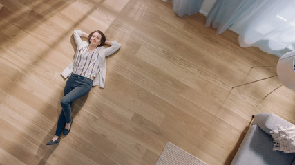 Young Woman is Lying on a Wooden Flooring in an Apartment. She's Dressed Casually. Cozy Living Room with Modern Minimalistic Interior and Wooden Parquet. Top View Camera Shot.