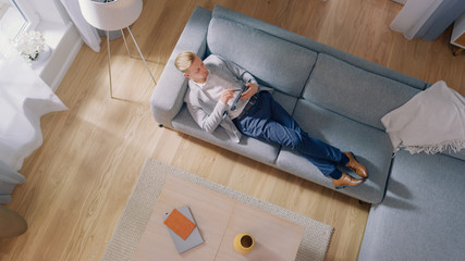 Young Man is Lying on a Sofa, Working or Sketcing on a Tablet Computer. Cozy Living Room with Modern Interior, Grey Sofa and Wooden Flooring. Top View Camera Shot.