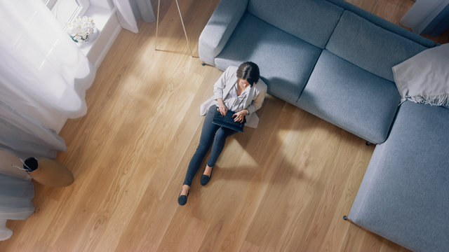 Young Woman is Sitting on a Floor, Working or Studying on a Laptop. Cozy Living Room with Modern Interior, Grey Sofa and Wooden Flooring. Top View Camera Shot.