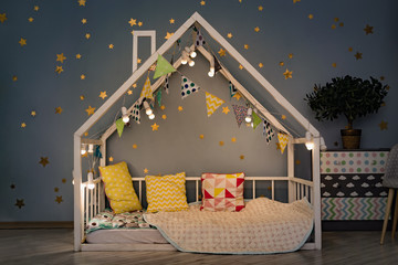 Modern kids bedroom in the evening. White house bed decorated with lights garland