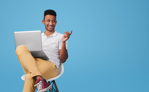Cheerful black hipster with laptop
