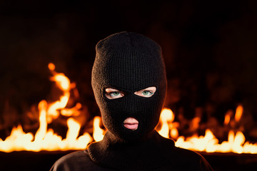 Portrait of young woman in black balaclava against backdrop of a blazing night fire. Concept of mass rallies and riots