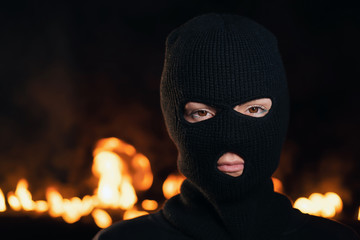 Portrait of young woman in black balaclava against backdrop of a blazing night fire. Concept of mass rallies and riots. Copy space