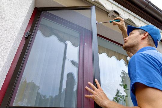 man installing mosquito net wire screen on terrace doors