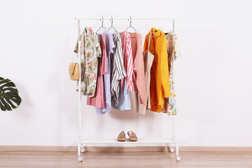 Women's hip clothing store interior concept. Row of different colorful female clothes hanging on rack in hipster fashion show room in shopping mall. White wall background. Copy space.
