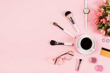 flat lay with cup of coffee, flowers, decorative cosmetics, credit card and accessories on pink