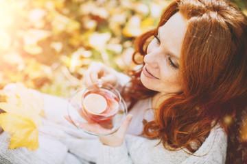 Portrait einer rothaarigen Frau im Herbst mit Blättern mit Teeglas trinkt Tee