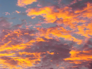 Dramatic sunset sky background with fiery clouds, yellow, orange and pink colors