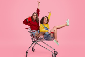 Cheerful sisters riding shopping trolley