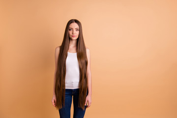 Close up photo beautiful amazing her she lady very long brown hair show great condition curls look confident interested curious wear casual white tank-top jeans denim isolated pastel beige background Wall mural