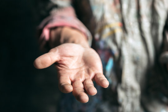 Male beggar hands seeking money, coins from human kindness on the wooden floor at public path way or street walkway. Homeless poor in the city. Problems with finance, place of residence.
