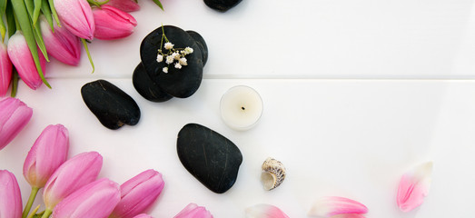 Aluminium Prints Tulip Spa setting with tulips , black stones and candle on white wood background.