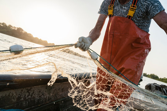 Dynamic composition with a fisherman dressed in an orange rompers gathering his trammel net during a fishing trip on the Danube river.