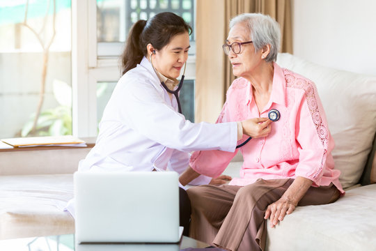 Family doctor or nurse checking smiling senior patient using stethoscope during home visit,young female home caregiver,health visitor examining asian elderly woman,healthcare medicine concept