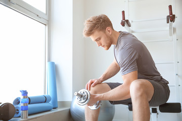 Sporty young man training with dumbbells in gym Fototapete