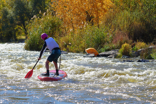 Sportsman paddling on rapids in whitewater river on a inflatable stand up paddle board (SUP)