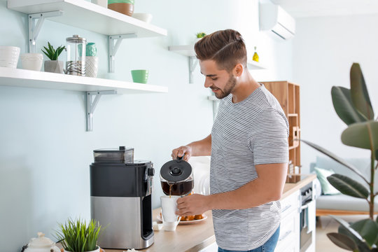 Handsome man using coffee machine in kitchen