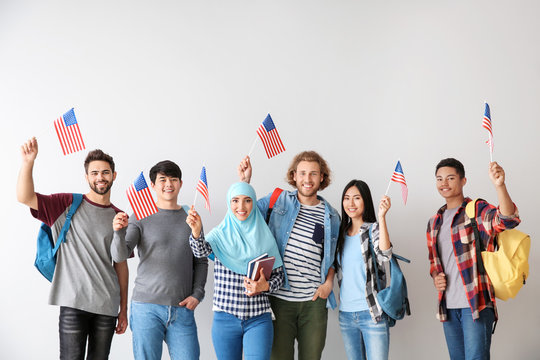 Group of students with USA flags on light background