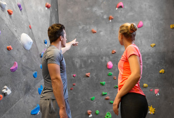 fitness, extreme sport and bouldering concept - man and woman exercising at indoor climbing gym