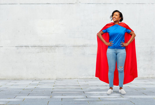 super power and people concept - happy african american young woman in superhero red cape over grey concrete background