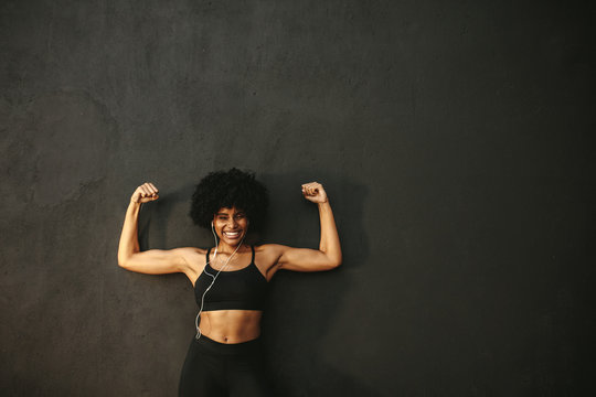 Smiling athlete flexing muscles