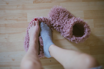 Early cold morning wake up! Woman's feet  standing on one (of two) home plush slippers - wearing woman one sock - POV picture