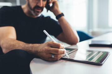 Businessman verifying reports on digital tablet