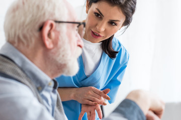 Selective focus of calm nurse talking to elderly patient