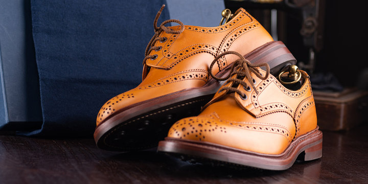Brown full grain leather brogues on wooden display in in men shoes boutique store with box and cloth shoe bags.
