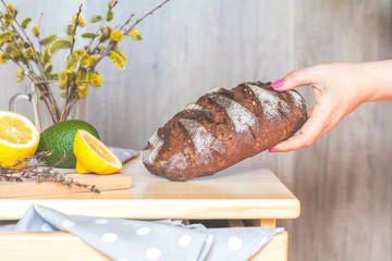 Woman puts homemade rye bread on the table
