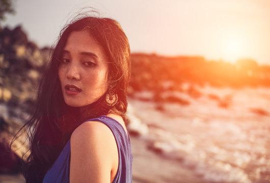 Asian girl wear Indigo dyed cotton on the beach,orange light flare.
