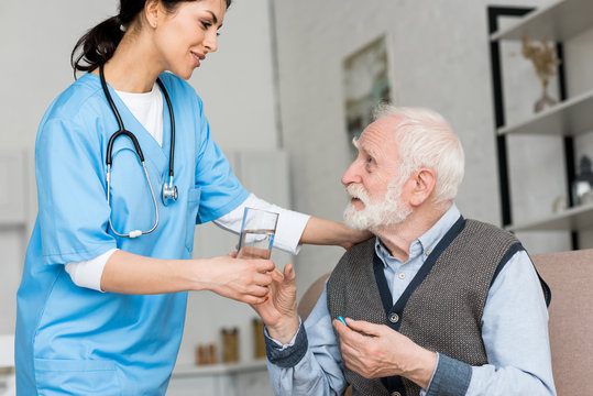Nurse giving glass of water to elderly man with pill in hand