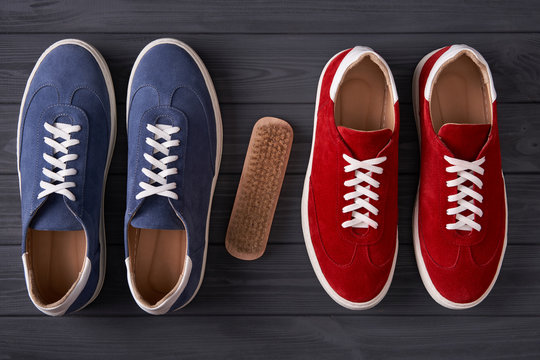 Top view of red and blue casual unisex suede sneakers with cleaning brush