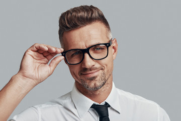 Handsome businessman. Good looking young man adjusting eyewear while standing against grey background Wall mural