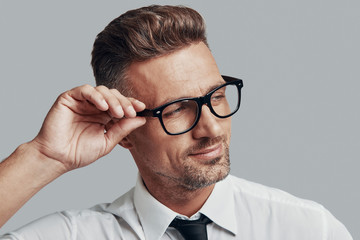 In his style. Good looking young man adjusting eyewear and smiling while standing against grey background